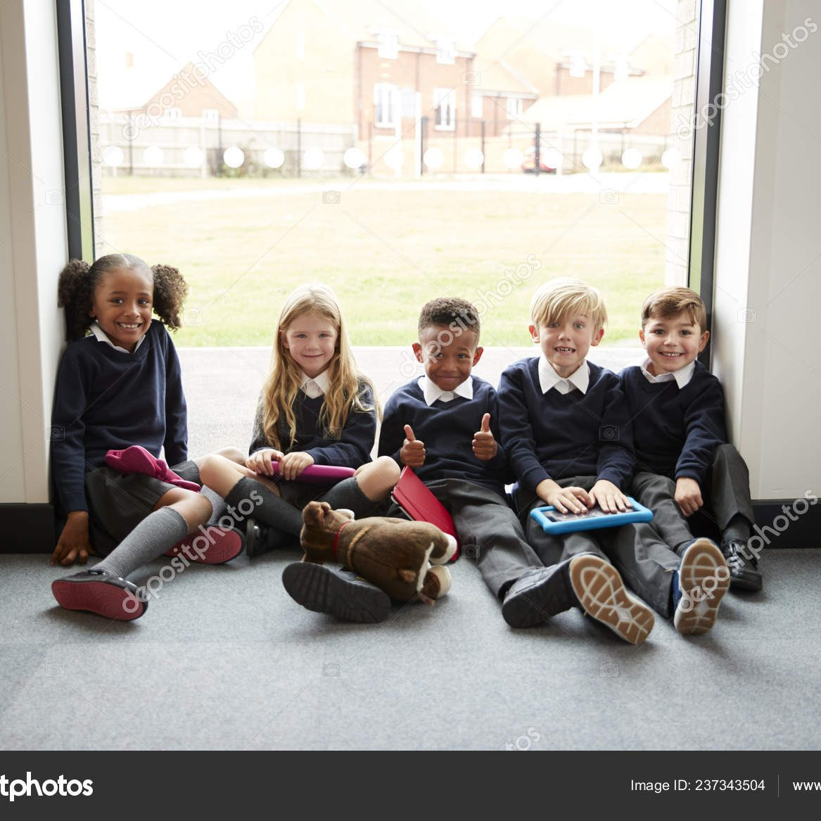Five primary school friends with tablet computers sitting on the floor in a school corridor at break time, smiling to camera, selective focus