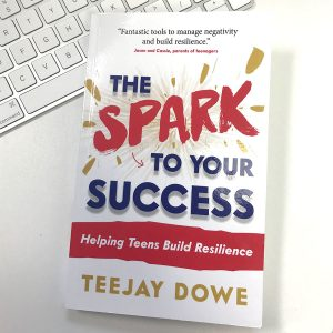 The Spark to Your Success book by TeeJay Dowe resting on a desk next to a keyboard